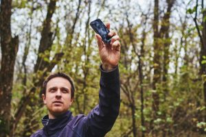 man holding up cell phone for better signal